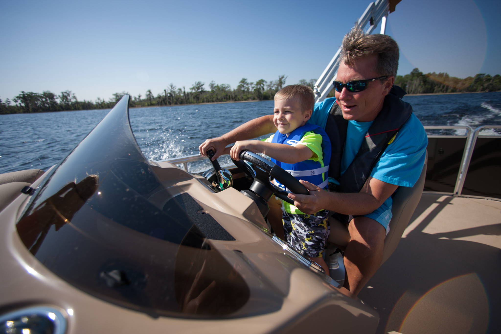 man and son driving pontoon rental boat